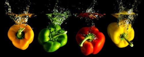 Glasbild Bunte Küche, Paprika in rot, gelb, orange und grün im Wasser